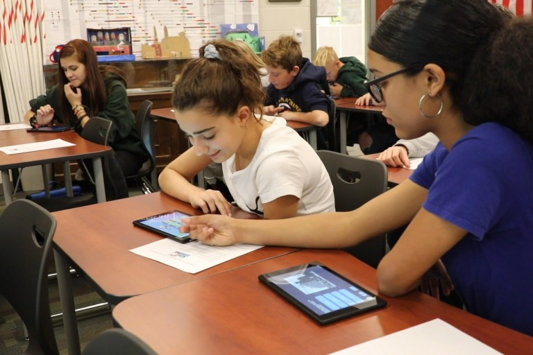 Middle school students sit at desks in a classroom working in the CitizIN app on tablets.