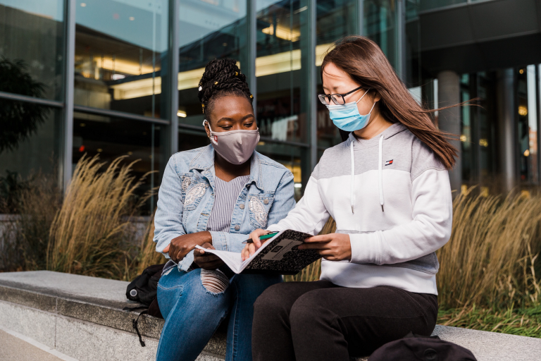 Two students wearing face masks sit down to study together on campus