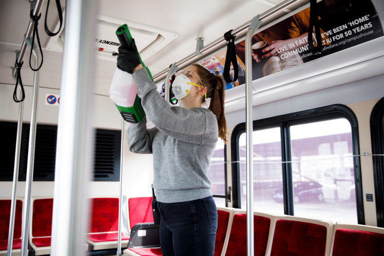 A student supervisor cleans an IU campus bus