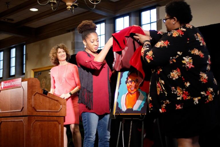 Ashley Smith and Monica Johnson take the cover off the painting, while Mrs. McRobbie looks on.