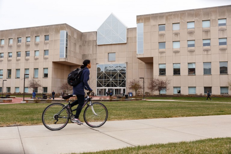 A woman rides a bike in front of University Library
