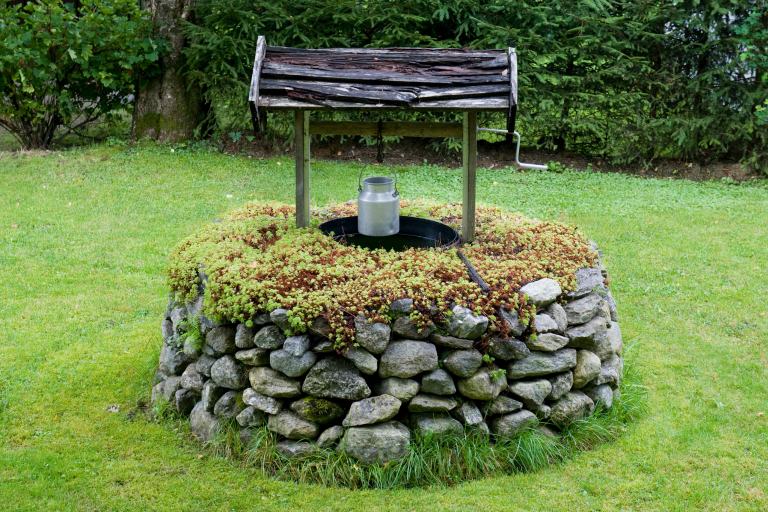 An outdoor well in the middle of green grass