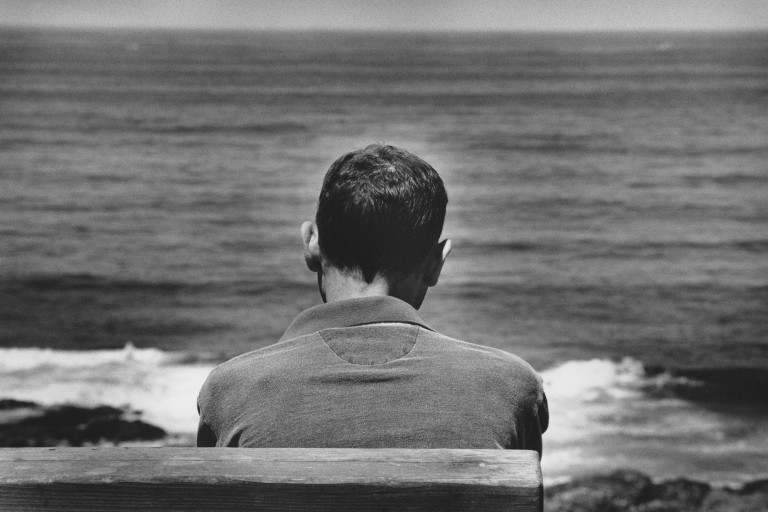 The back of a person's head as they are facing the ocean
