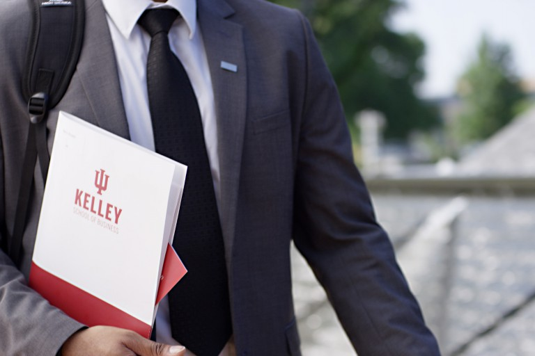 Kelley student carries a folder.