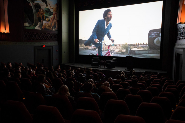 An image of a man on a bike on the IU CInema screen, with audience members in the seats.