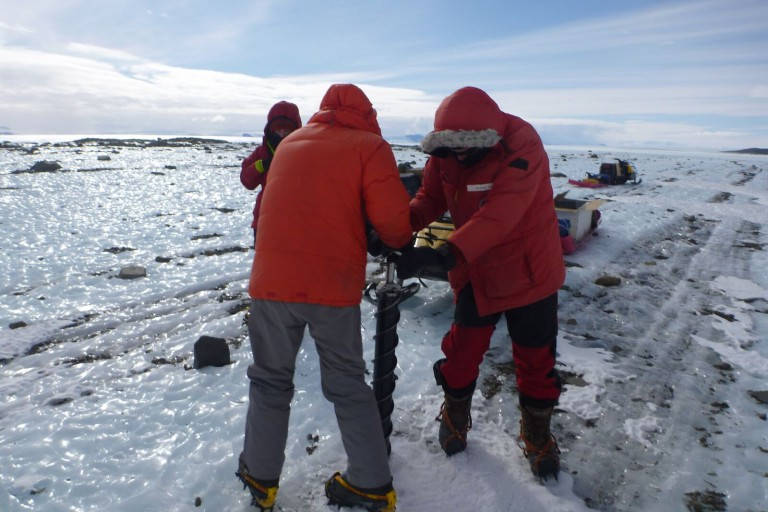 Team members taking an ice core sample