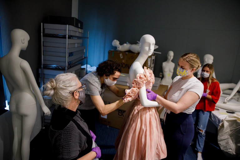Students adjust a pink silk organza dress on a mannequin