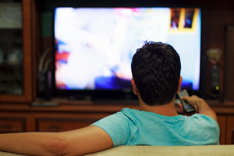 Man watches television with remote control in his hand