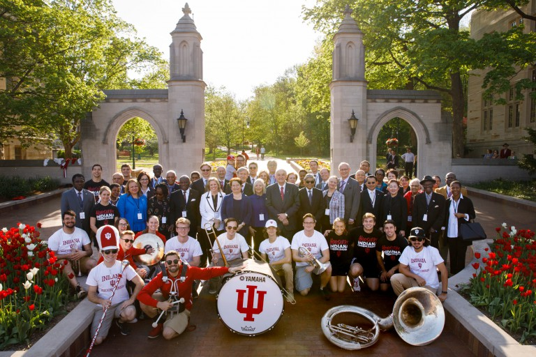 IU leaders and IU Crabb Band members pose with about 30 foreign ambassadors in front of Sample Gates
