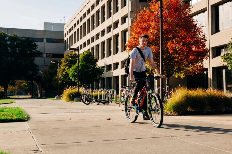 An IUPUI student bikes through campus