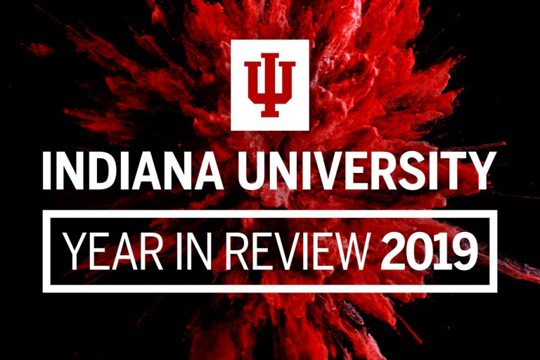 "Words say ""Indiana University, Year in Review 2019"" and a splash of red is behind it"