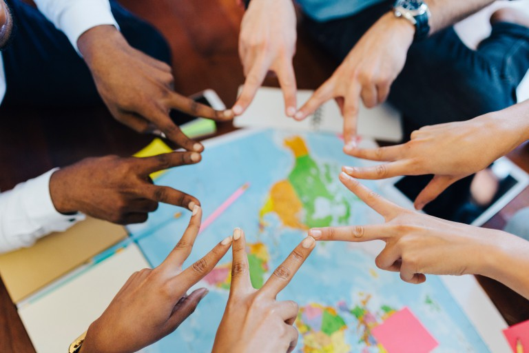 Hands making peace signs over a map