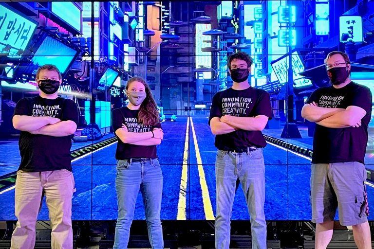 Four students in matching T-shirts stand with their arms crossed in front of a huge video screen