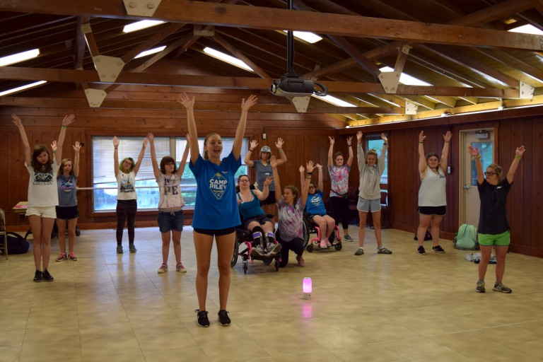 Ballet dancers raise their arms in the air