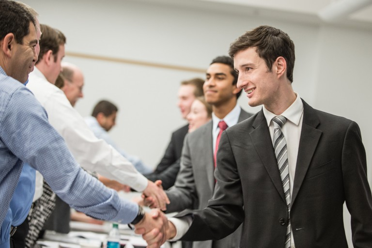 Several students shaking hands with visiting business people