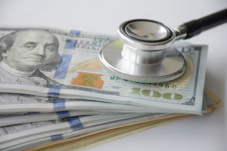 A stethoscope rests on top of stacks of $100 bills