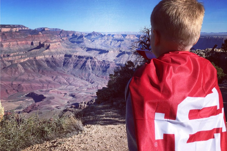 A child with an IU flag draped over his shoulders looks out over the Grand Canyon