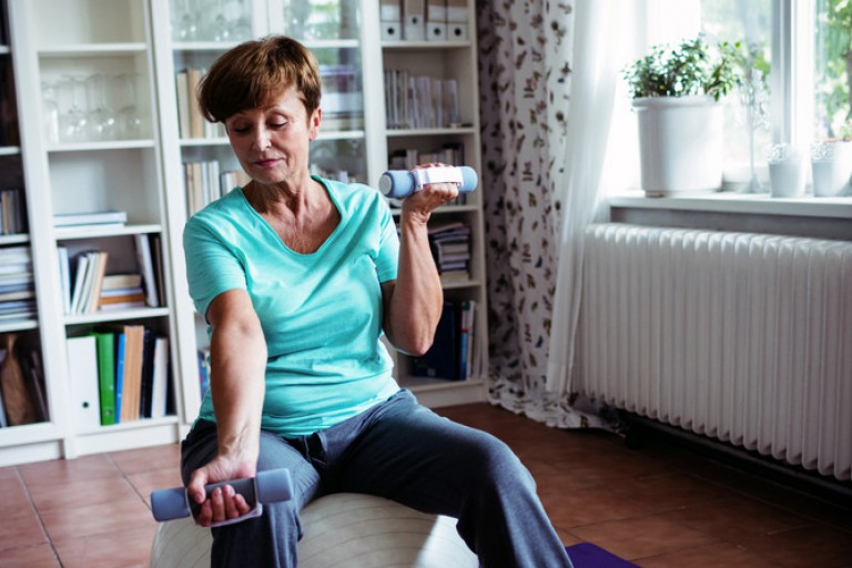 Older woman sitting on an exercise ball performs bicep curls