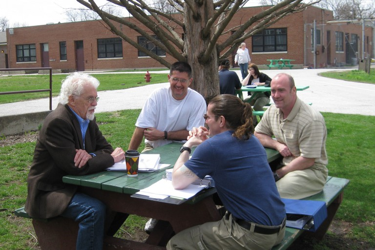 Occupational therapy associate professor Jeffrey Crabtree sits with former prison inmates.