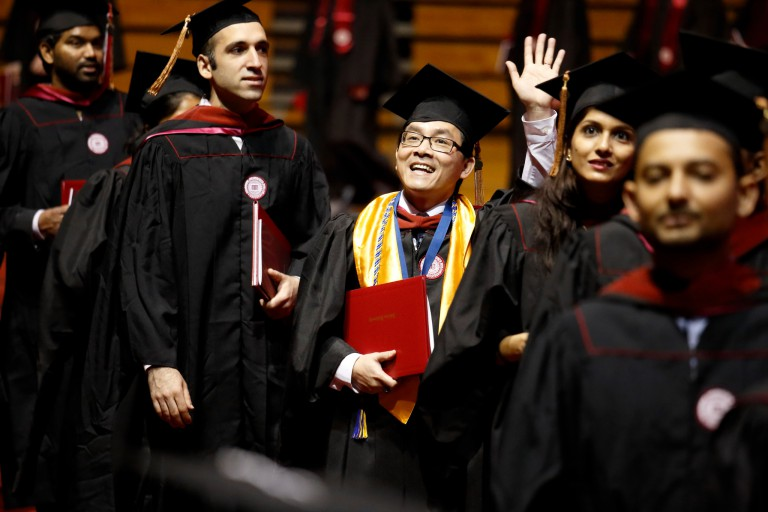 A graduate waves during commencement