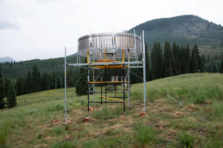 An instrument to collect weather data sits in a field with a mountain in the background