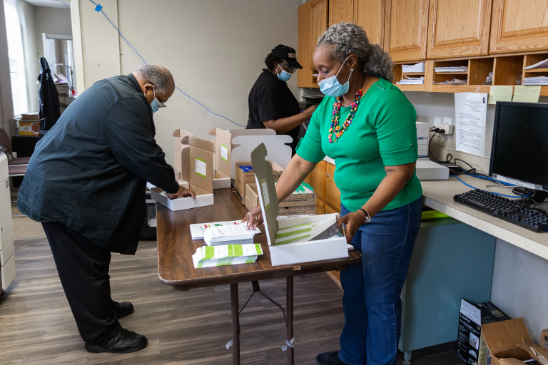 Church employees stand at a table filling boxes for the lead test kits