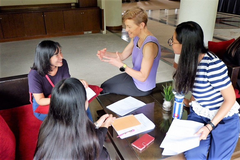 Katherine Welch, founder of Relentless, sits on a table speaking to three young women