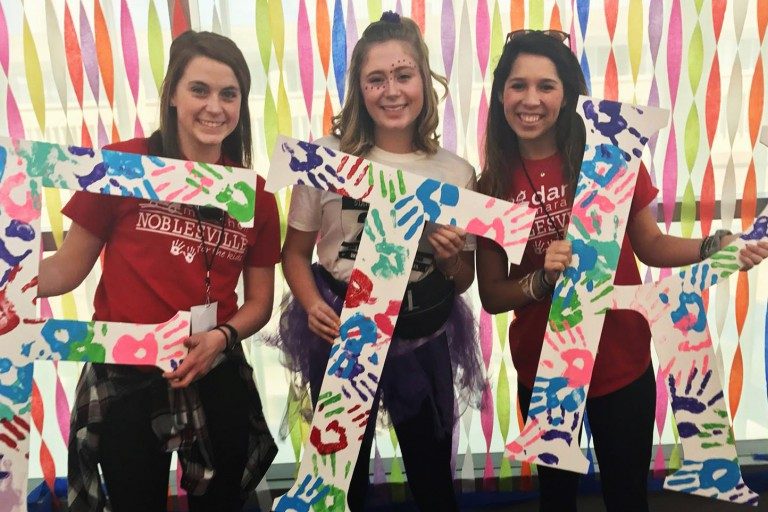 """Three female students hold FTK signs representing """"For the Kids."""