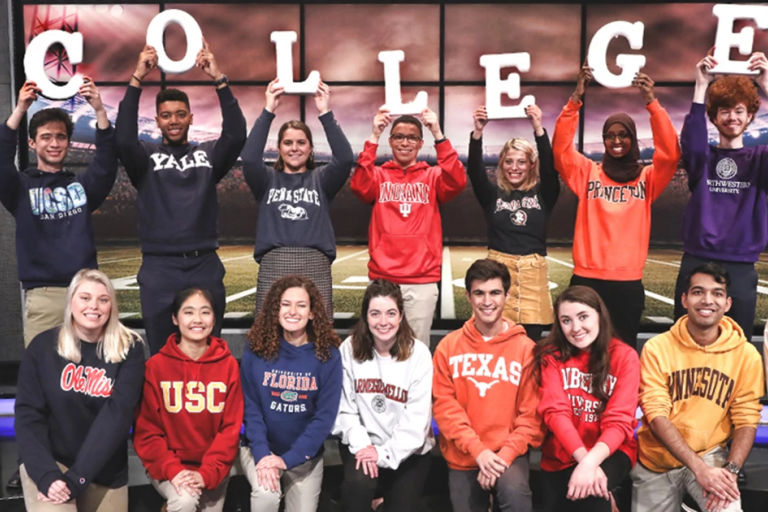 Tyler Combs on the Jeopardy set with other college contestants, holding up the word COLLEGE