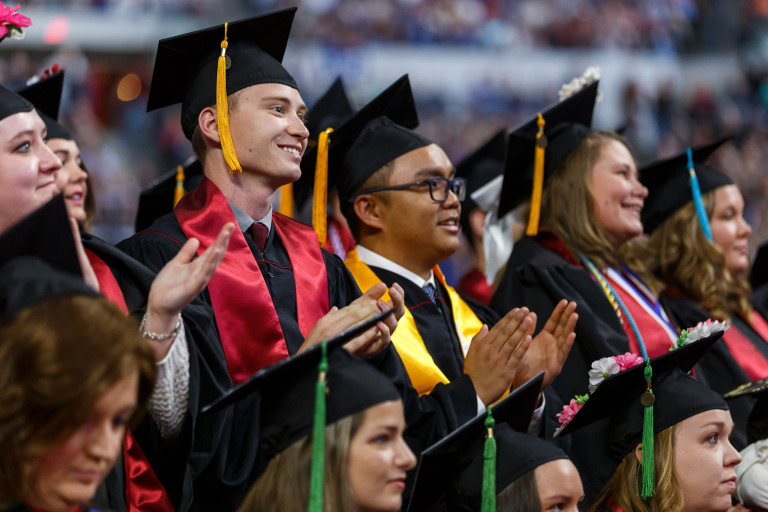 IUPUI students in caps and gowns clapping during a commencement ceremony