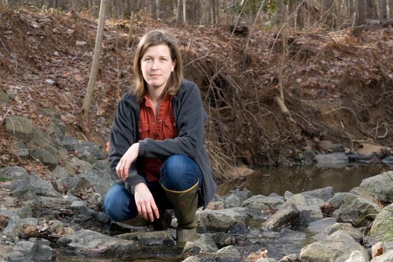 Emily Bernhardt kneeling in a stream