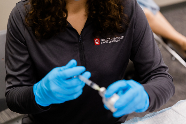 Closeup of hands prepping a vaccine