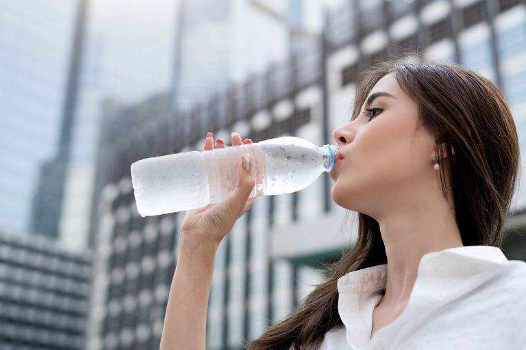 A woman drinks from a water bottle