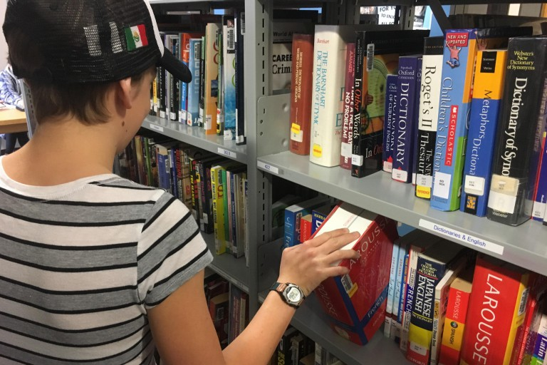 Student pulling a dictionary off a bookshelf