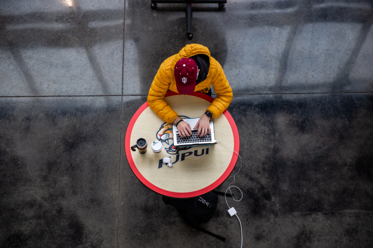 a student studies at a table on the IUPUI campus