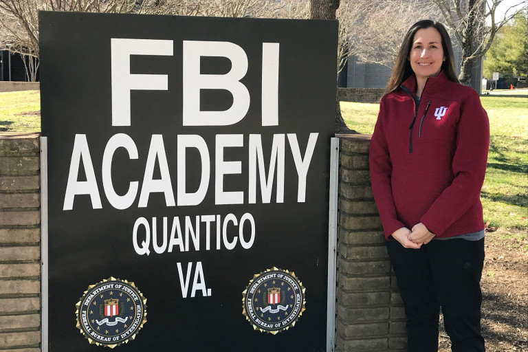 Jill Lees stands in front of a sign at the FBI National Academy