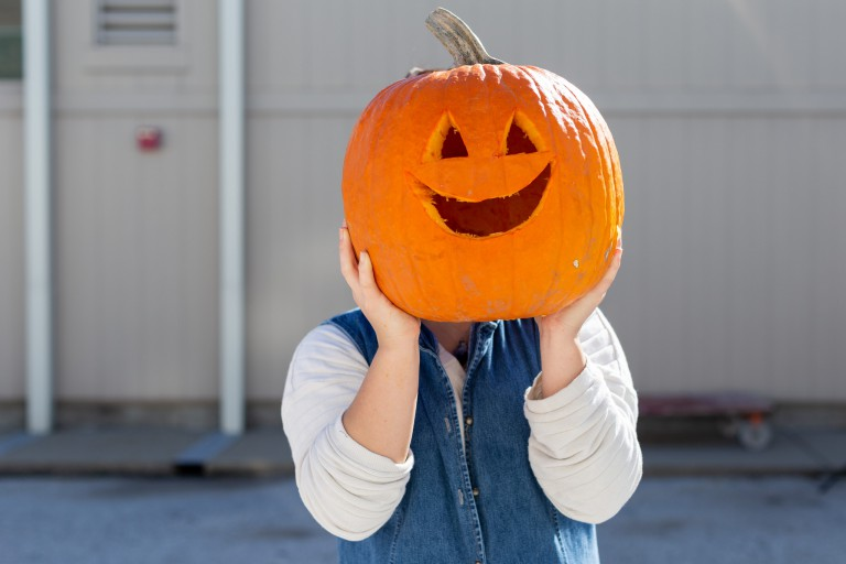 Student holds a carved pumpkin.