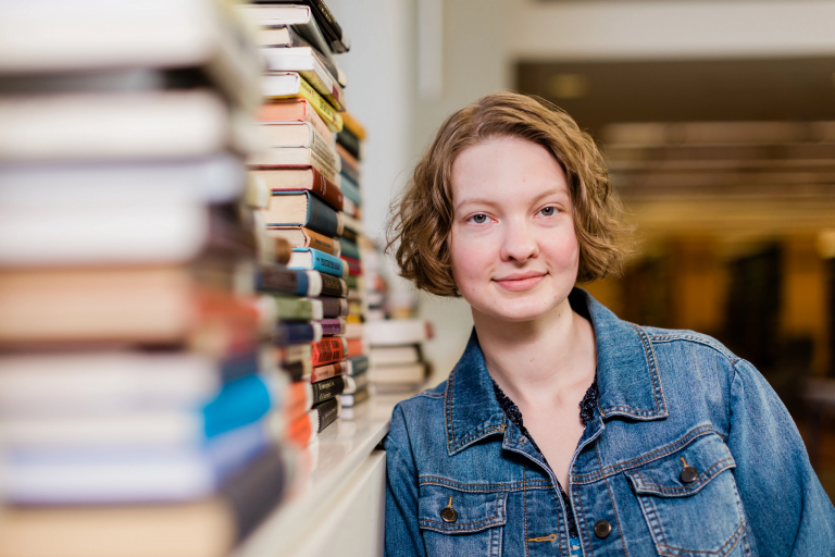 IUPUI student Eden Rea- Hedrick standing near a shelf of stacked books.