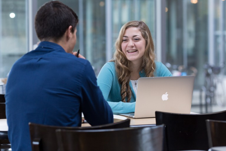 IUPUI's Sarah Grace Fraser speaks with a fellow student at a table.