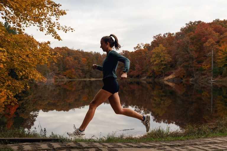 Olivia Ballew running past a lake in the fall