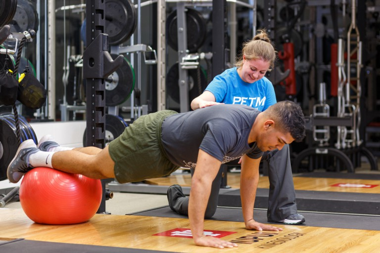 A man works out with help from a student in the strength conditioning lab.