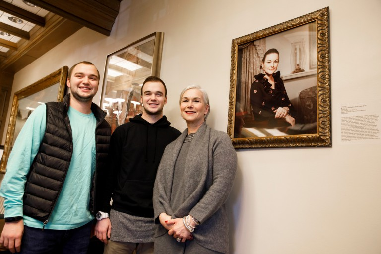 Andrew Gutman, left, Phillip Gutman and Gretchen Gutman pose with a framed photo of Carolyn Gutman.