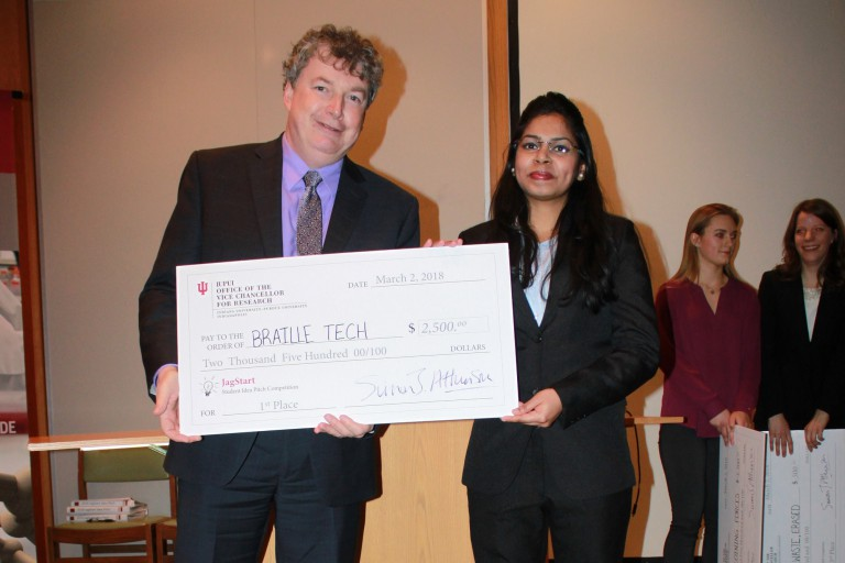 Madhura Mhatre holds her giant check with IUPUI VC for Research Simon Atkinson