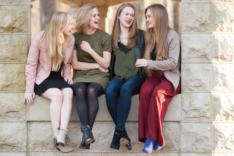 Leah, Katherine, Tricia and Christina sit on a wall laughing together.