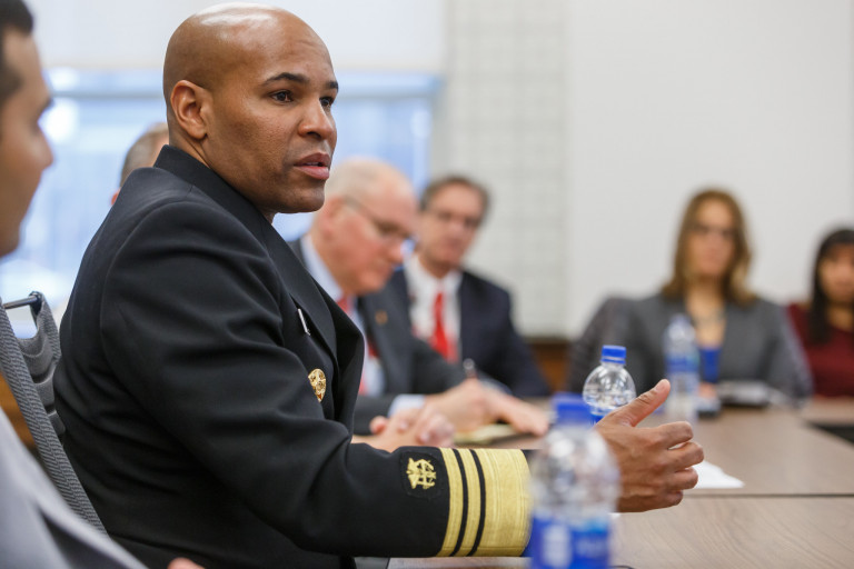 U.S. Surgeon General Jerome Adams speaks to a group of people while seated at a table.
