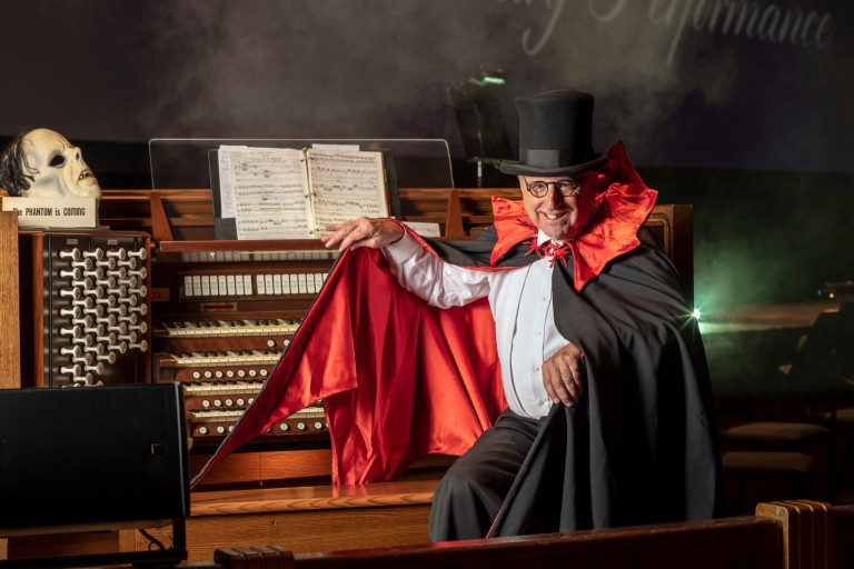 Dennis James wears a costume while posing in front of a pipe organ.