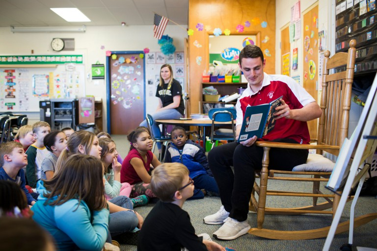 IU soccer player Sean Caulfield reads to students at Arlington Elementary School.