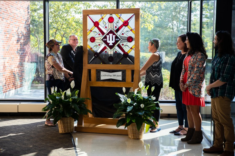 An unveiling of a piece of stained glass created by IU Southeast students