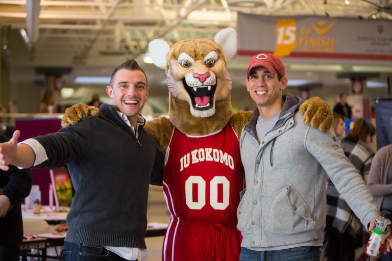 IU Kokomo's Kingston Cougar mascot stands with arms around two male students.