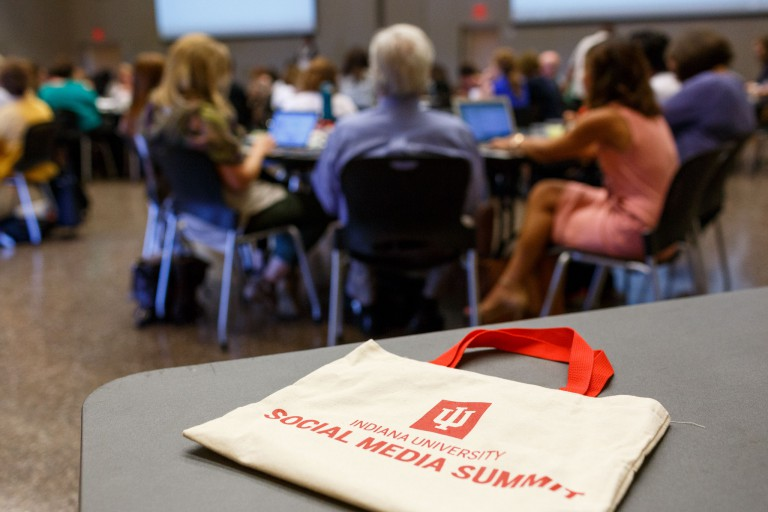 An IU Social Media Summit bag lies on a table in the foreground, with summit attendees in the back
